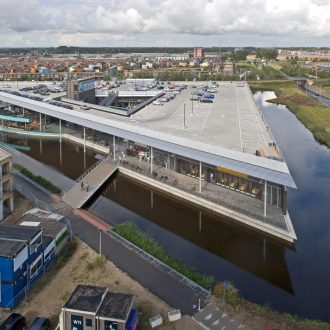 Winkelcentrum Weidevenne met parkeerdak, appartementen en station in Purmerend